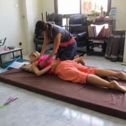 Two people practice Thai massage
