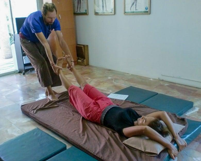 Man pulls legs during Thai massage
