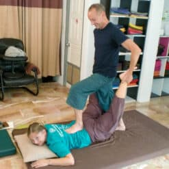 Foot press on back during Thai massage