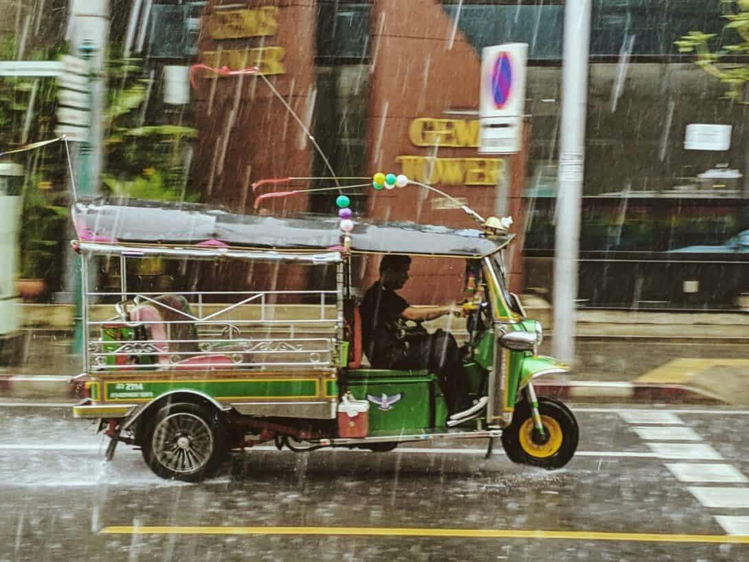 Man drives tuk tuk in rain.