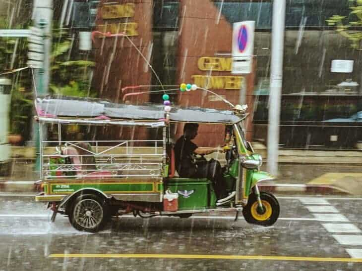 Man drives tuk tuk in rain.