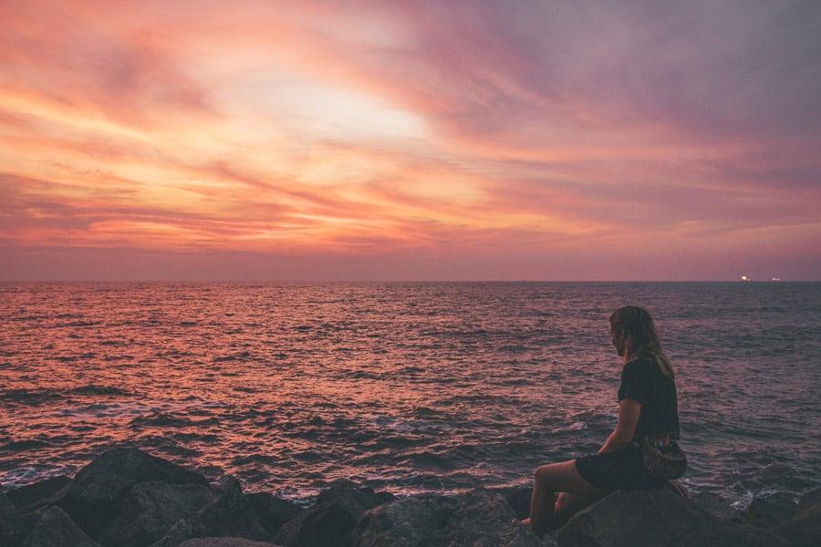 Girl watching sunset over the ocean in Miri, Borneo.