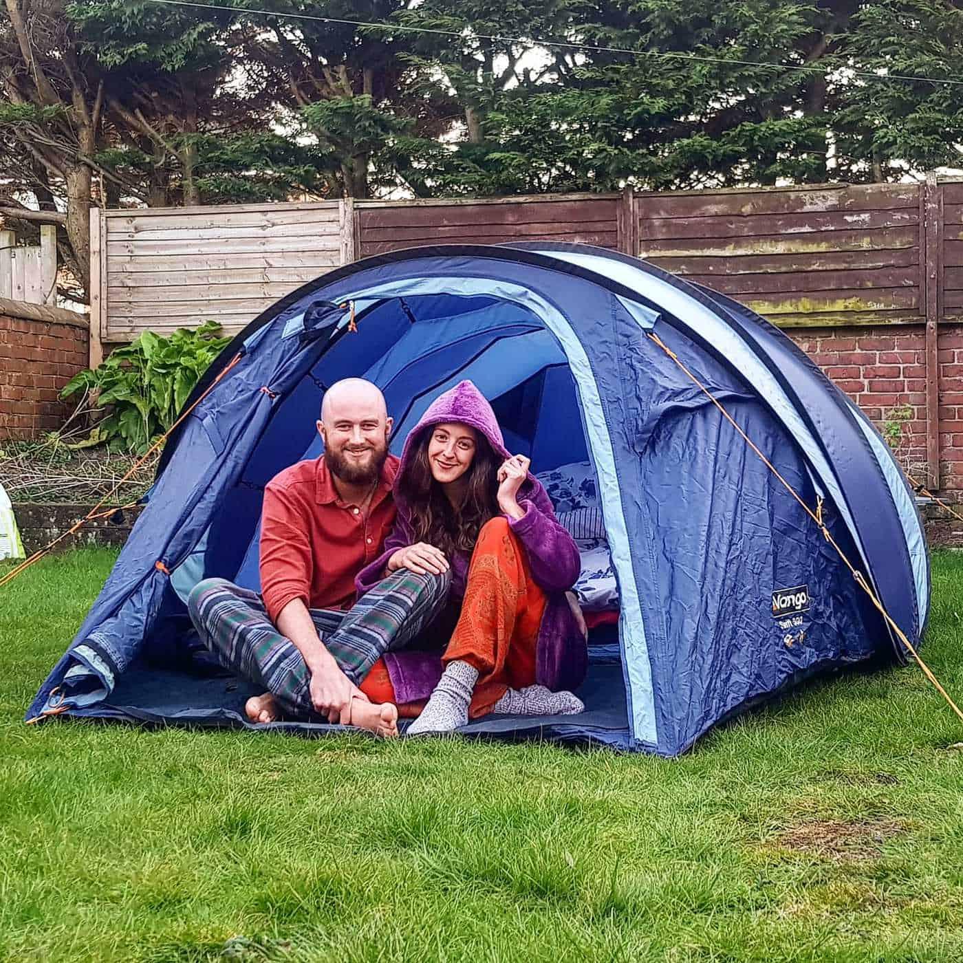 A couple camping in their back garden.
