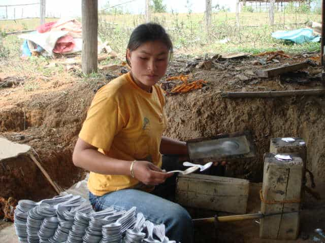 A villager near Phonsavan in Laos makes spoons from UXO war scrap.