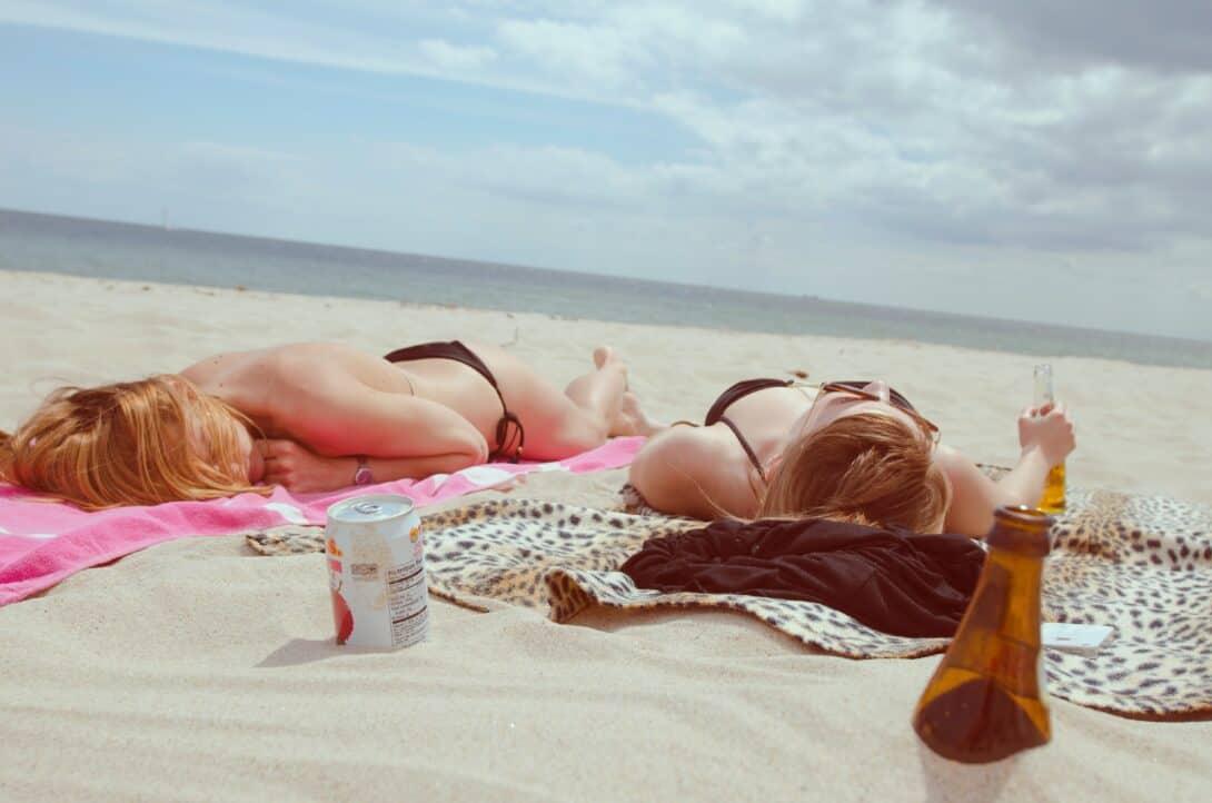 Two girls sunbathing on a beach