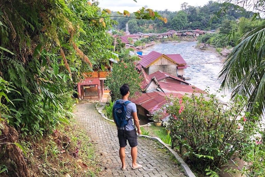 A traveller walking through Bukit Lawang, Indonesia.