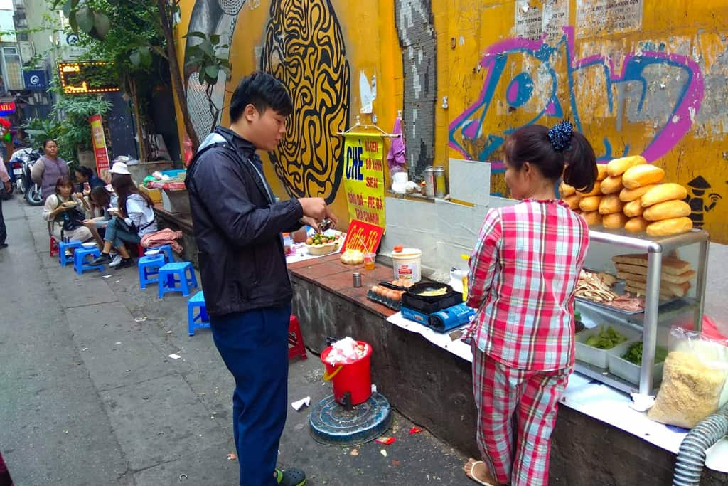 Lady serves Banh Mi on street in Hanoi