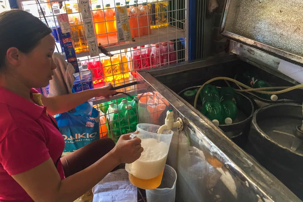 Lady filling Bia Hoi jug in Vietnam