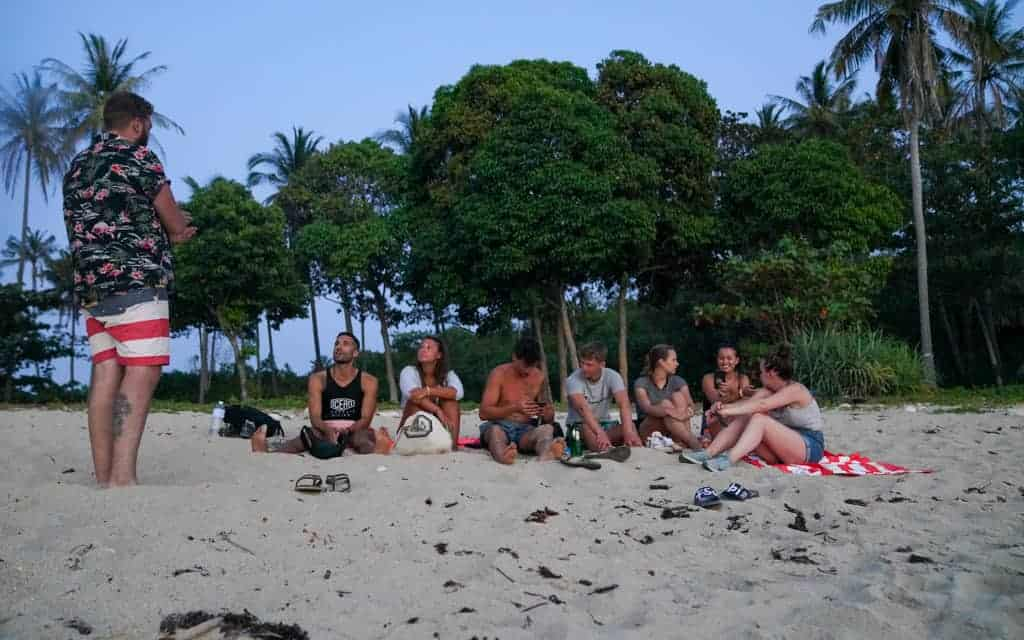 Backpackers chilling on beach together
