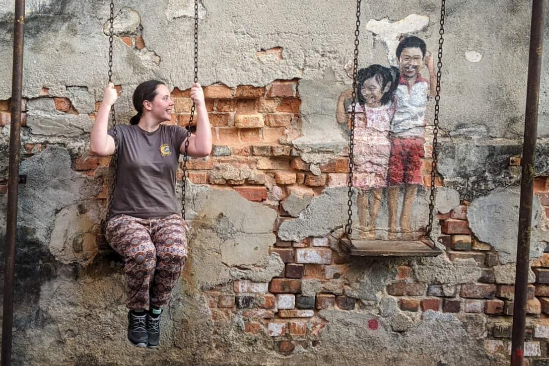 Girl sitting on swing at street mural, Penang
