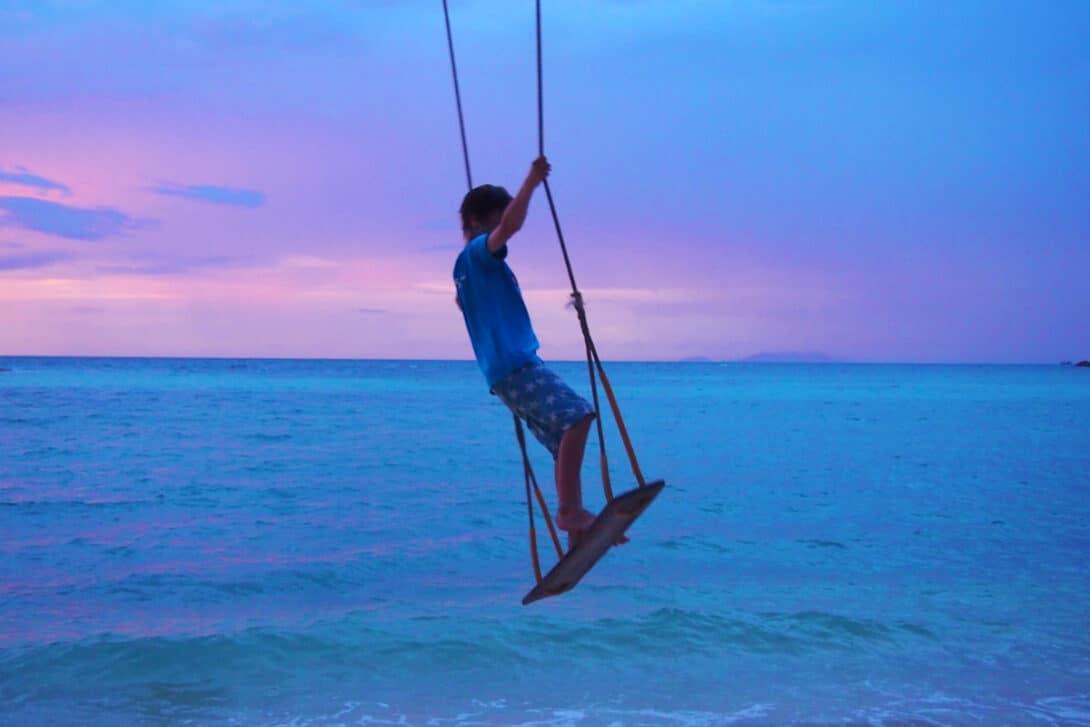Boy swings with ocean scenery