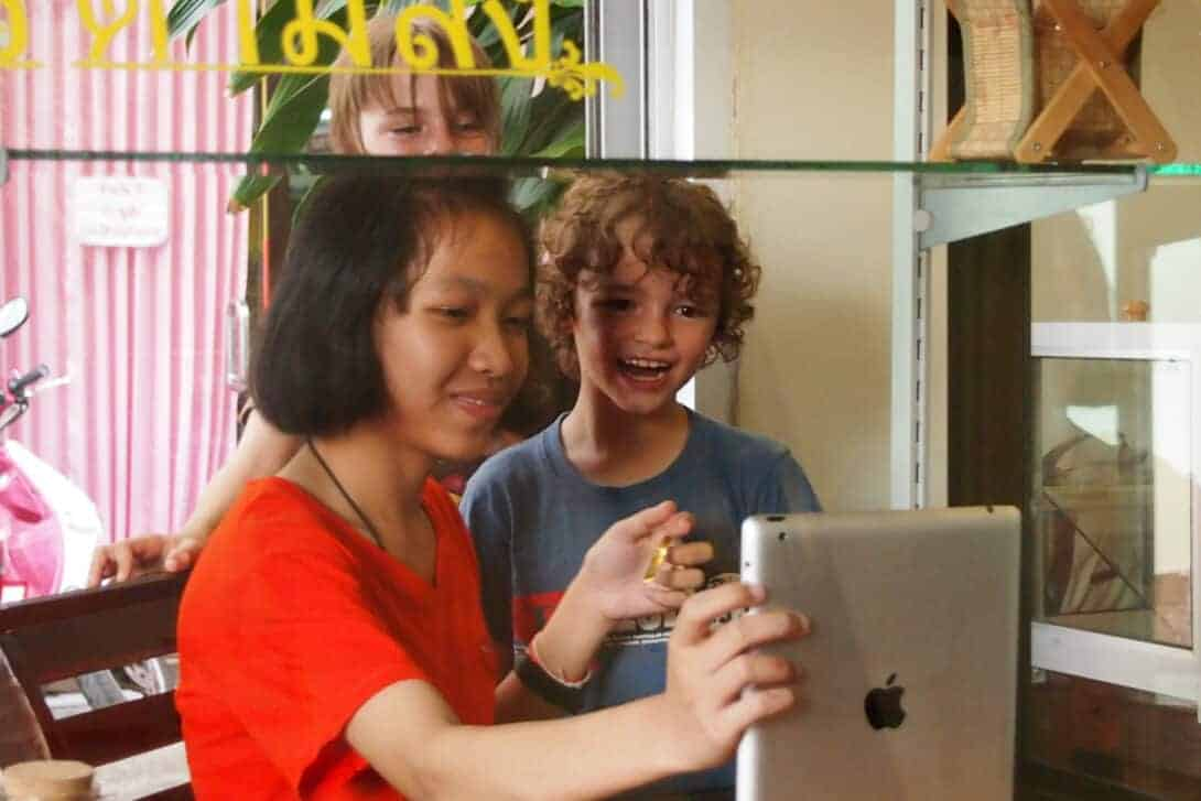 Two kids with Thai lady and iPad